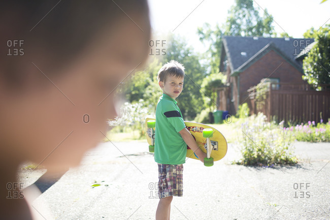 Little boy holding his skateboard looking at another child
