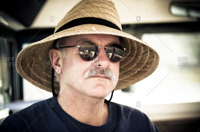 Portrait of Jim Roberts in sunglasses and straw hat on Lake San Antonio, California, USA
