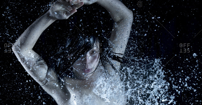 Portrait of young  woman dancing under falling water