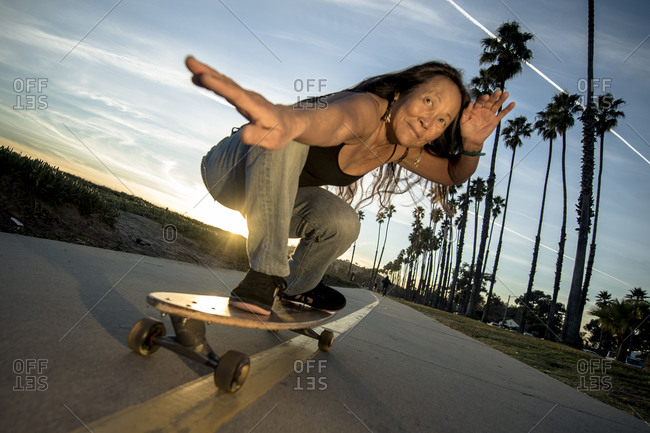 Womani posing on skateboard in sunset