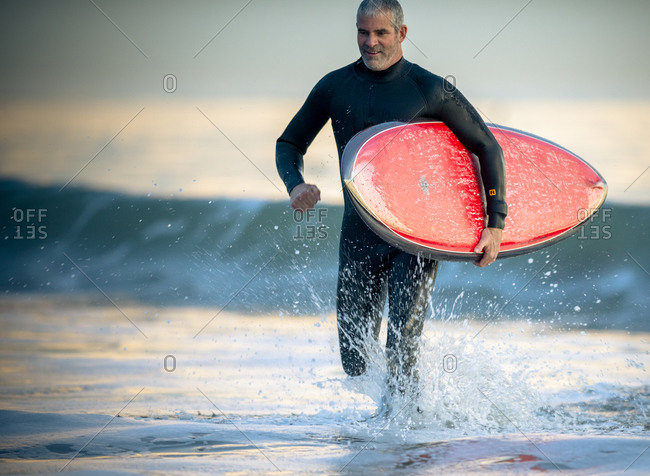Happy middle aged  man running with surfboard