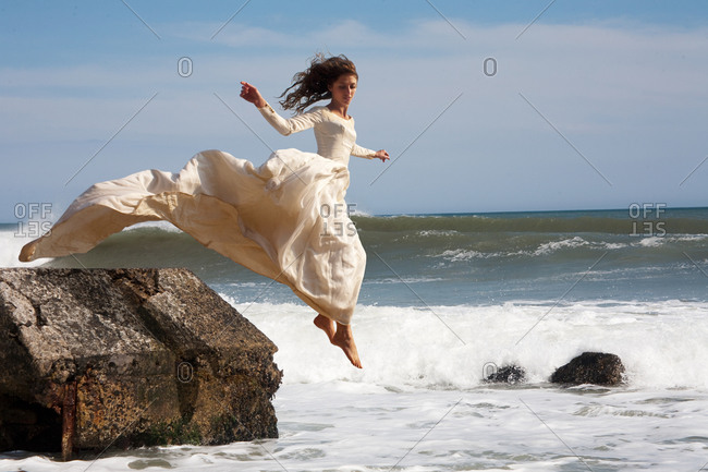 Young bride jumping off a rock