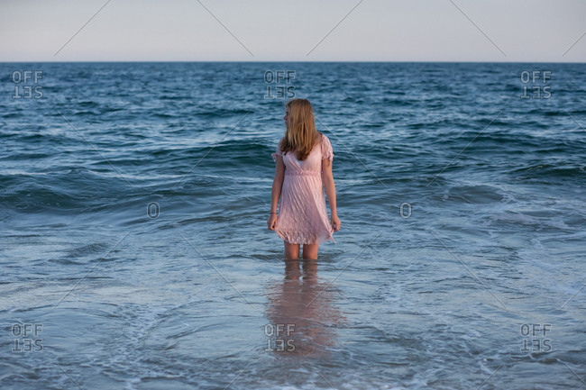 Girl in a pink dress standing in the water