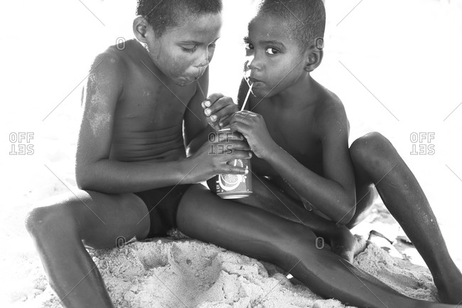 Portrait of little boys sitting in sand drinking with straw from beverage can
