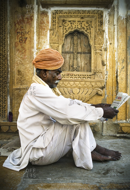 Indian man sitting on the floor and reading newspaper