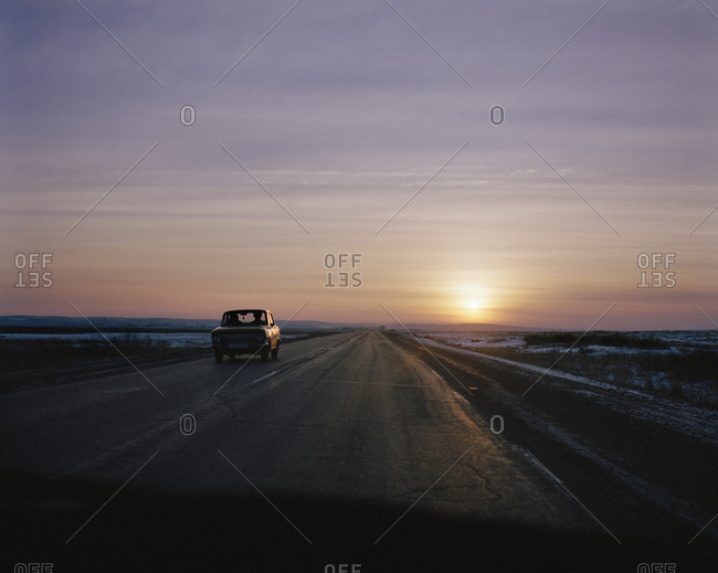A Russian Travant Car Driving On A Road At Sunset, Seen Through The Windscreen Of A Car Traveling In The Opposite Direction
