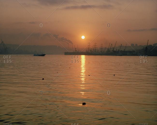 Boats And Bottles Floating In Golden Horn Bay At Sunset In Vladivostok