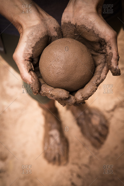 Close up of hand holding wet mud ball