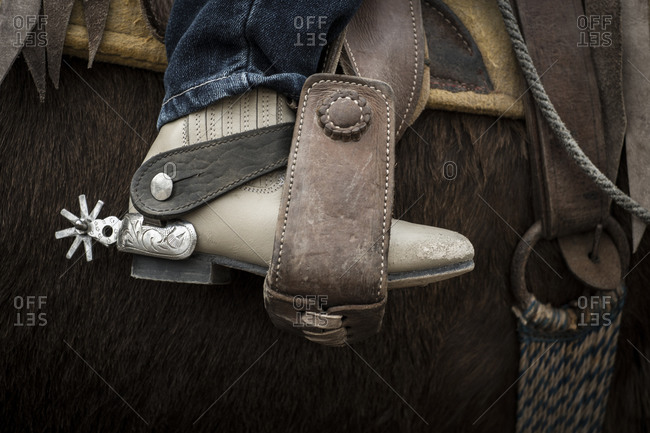 Close up of leather boot with spur in stirrup