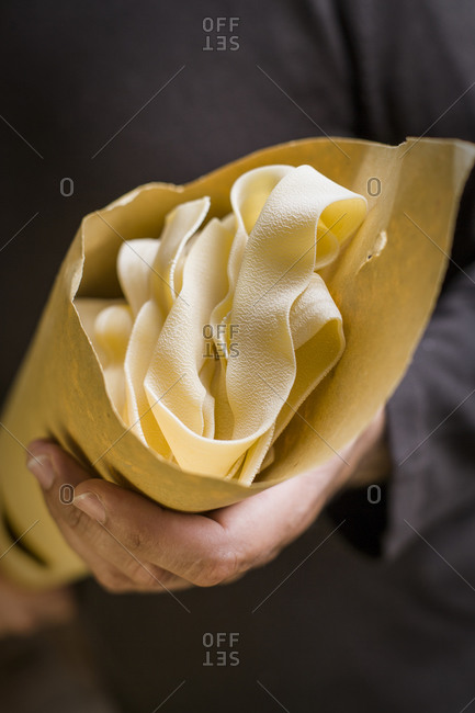 Close up of a hand holding tagliatelle pasta wrapped in paper