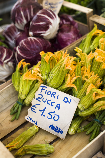 Bunch of fresh zucchini flowers in wooden crate on market
