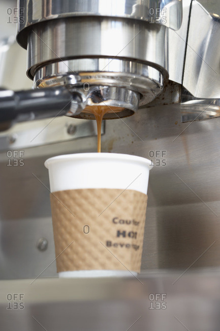 Close up of a shot of espresso pouring into a white paper cup