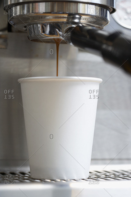 Pulling a shot of espresso into a white paper cup