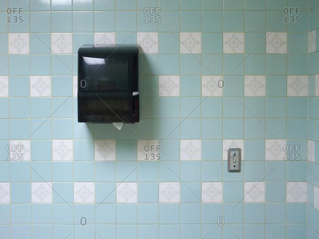 Paper towel dispenser and blue ceramic tiles of public man�s room
