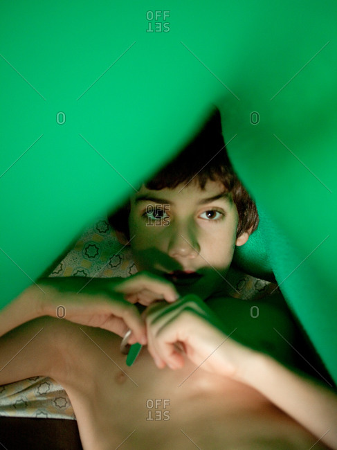 Young boy in bed in morning under tent made from blanket