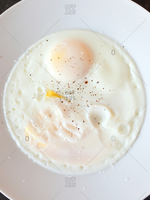Two fried eggs on plate seasoned with black pepper