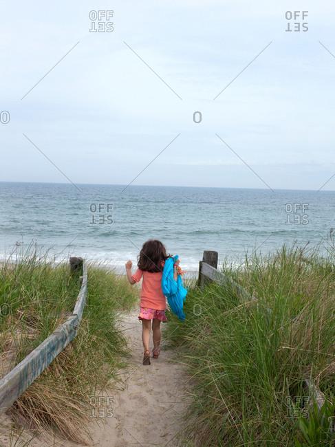 Young girl enthusiastically entering beach