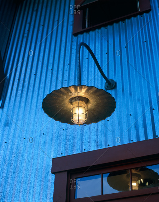 Detail of contemporary country style outdoor light above entrance way at dusk