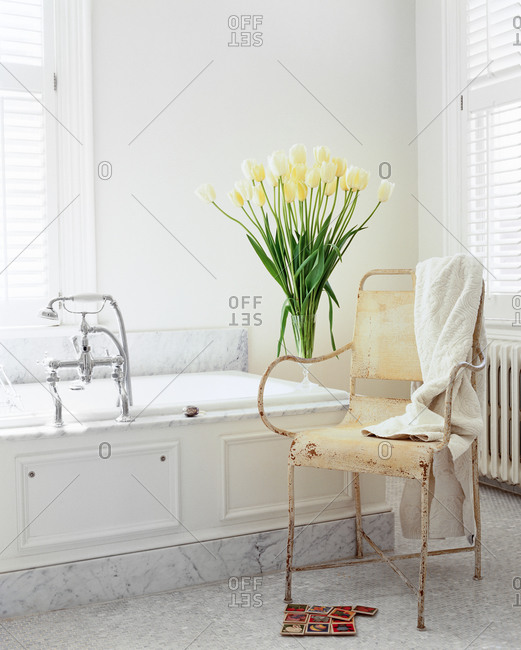 Modern shabby chic white bathroom with marble, white tulips and old garden chair