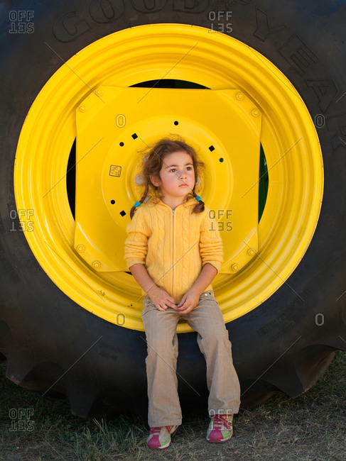 Young girl sitting on large yellow truck wheel and staring away pensively