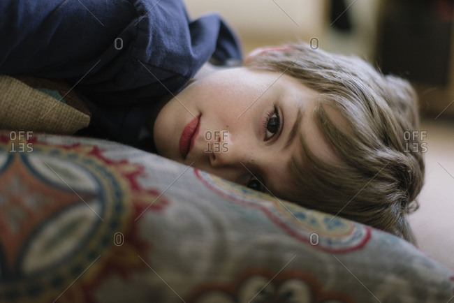 A little boy resting in a living room
