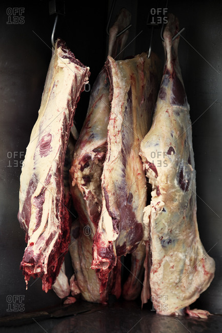 Four sections of butchered pig hanging on meat hooks