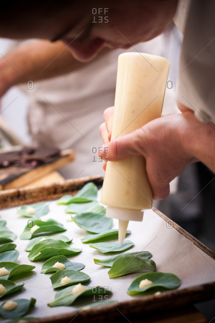 Side view of woman putting mayonnaise onto sage leaves