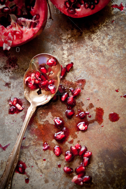 Red pomegranate arils on rusty surface