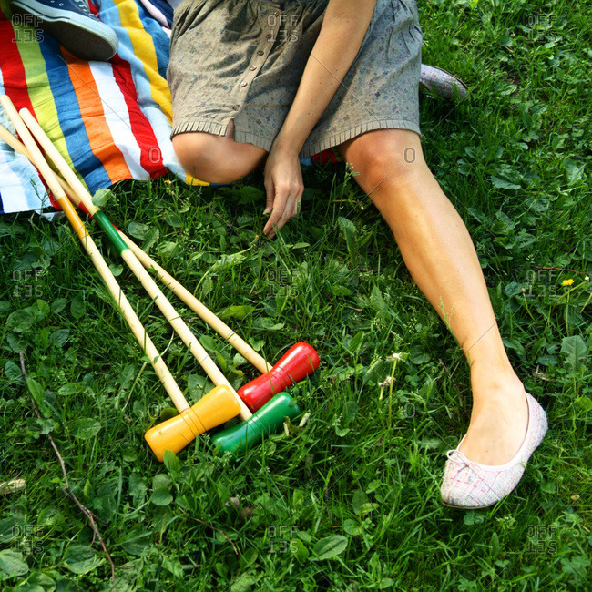 Girl sitting in the grass after palying croquet