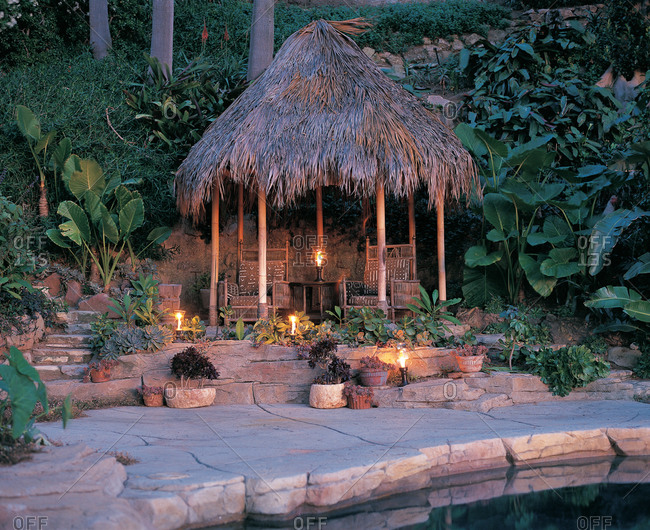 Tiki hut at pool side at dusk with candles and garden plants