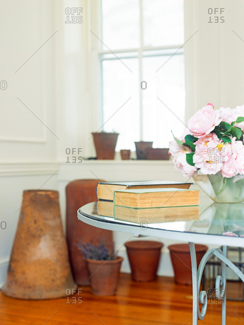 Room interior with glass table, rose bouquet and flower pots