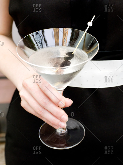 Woman holding glass of martini garnished with olives