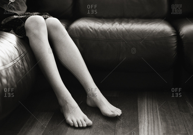 the legs and feet of a woman sitting on a sofa