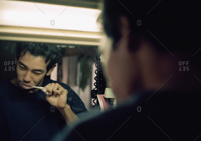 Reflection in mirror of man brushing his teeth