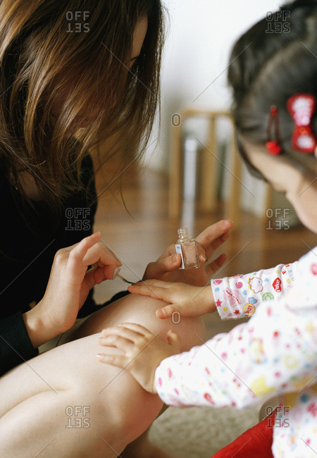 mother painting daughter's fingernails