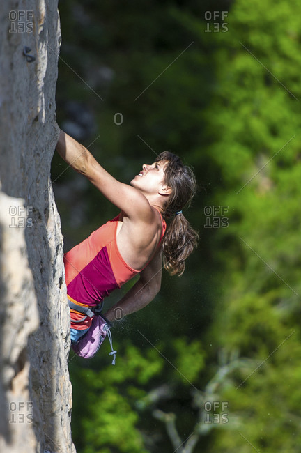A close up view of a woman reaching to her chalk bag during a demanding limestone climb.