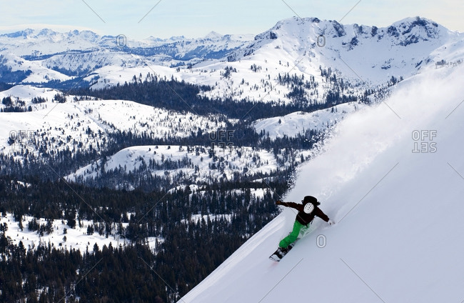 A snowboarder rips a huge turn in deep powder on Red Lake Peak off of Carson Pass near Lake Tahoe, CA.