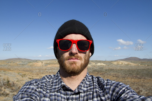 A male surfer with a beard wearing red sunglasses and a back beanie takes a  self-portrait during a surf trip in Central Baja 61d04acceb4f