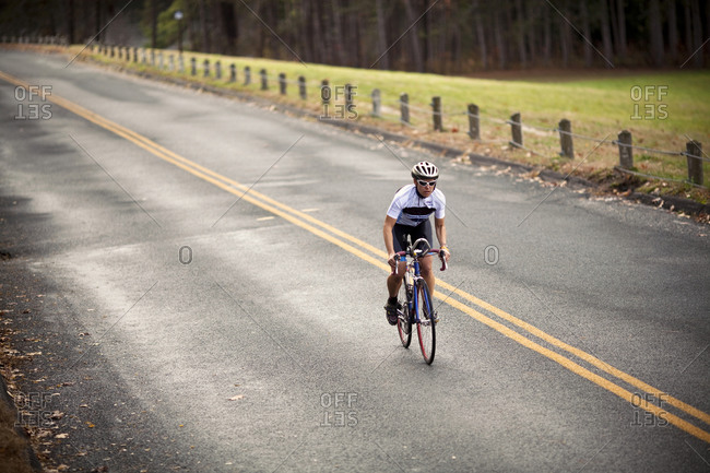 A female cyclist sprints up a hill on her bike while riding on a country road.