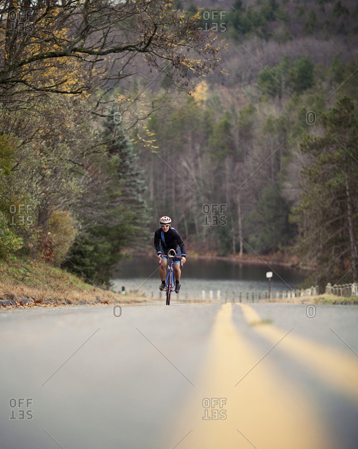 A female cyclist sprints up a hill while on a bike ride.