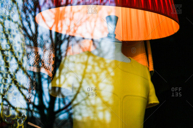 Short-sleeved, yellow cloth on dress form with red lampshade in show-window