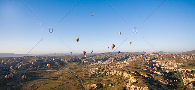 Hot air balloons flying over rocky rural landscape
