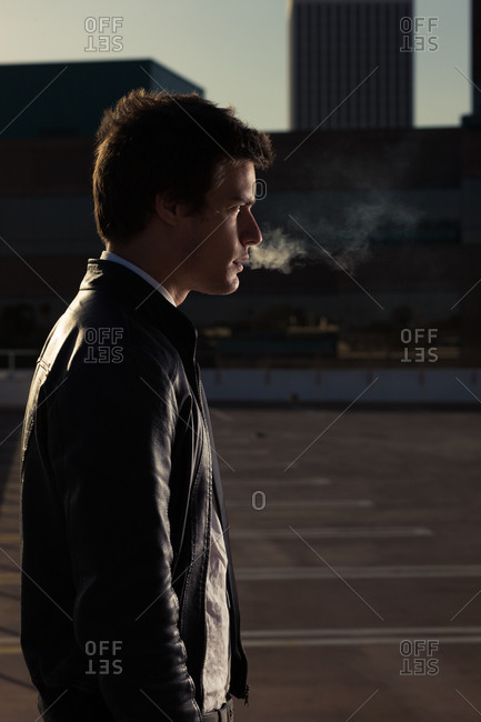 a portrait of a young man in a leather jacket smoking a cigarette