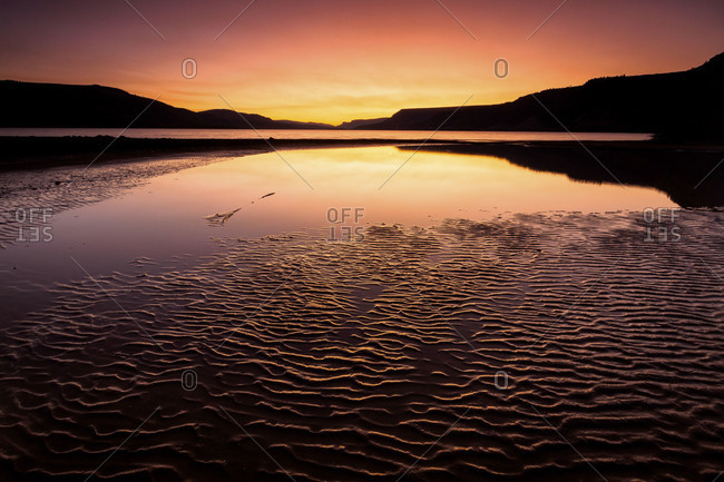 A view of a sunset behind a lake