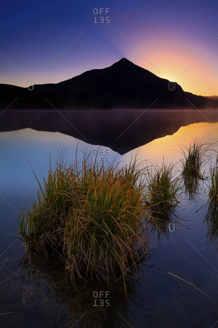 A reflection of mountain in a lake with tuft of grass