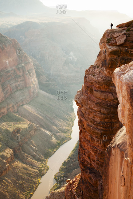 A photographer stands on the edge of Grand Canyon at Toroweap
