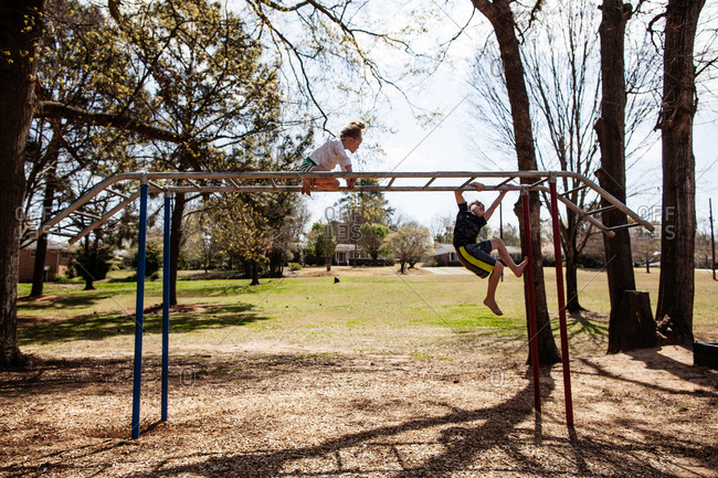 two kids playing on monkey bars