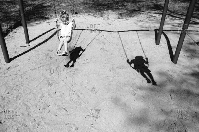 A 4 year old girl swings with her brother's shadow
