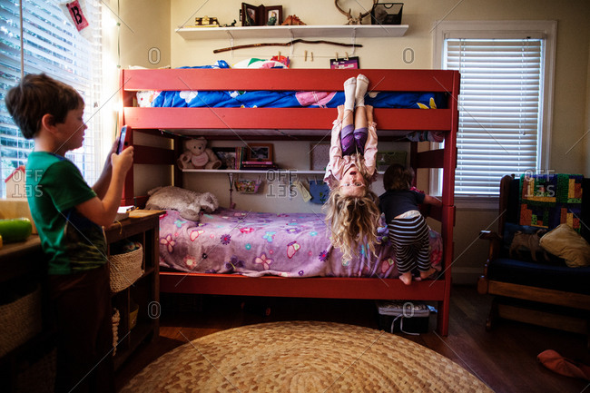 A girl hangs upside down on her bunk bed while her brother takes a photo with a cell phone camera