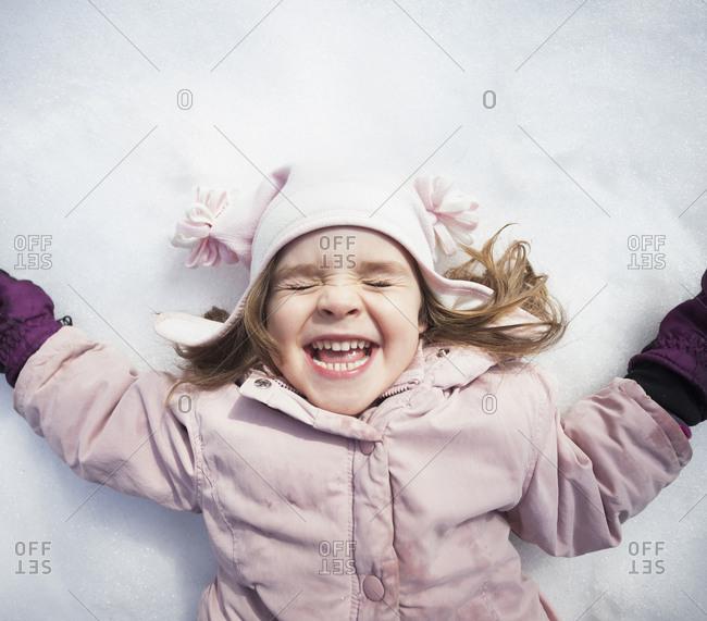 Portrait of Girl (2-3) lying down on snow